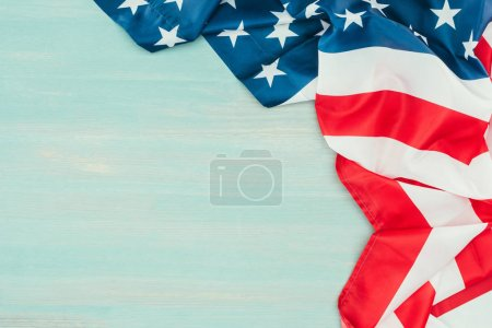 close up view of folded american flag on blue wooden tabletop, presidents day concept