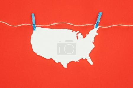 top view of piece of blank paper in shape of map hanging on rope isolated on red