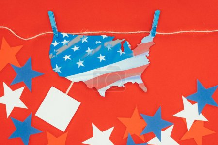 top view of piece of map with american flag hanging on rope and stars isolated on red