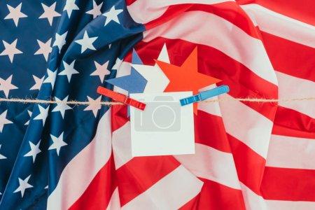 tendido plano con bandera americana, estrellas y papel en blanco colgando de la cuerda, concepto de día de presidentes