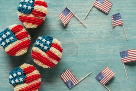 Photo pour Lay plat avec cupcakes arrangés et des drapeaux américains sur bois concept sur table, de la célébration du jour présidents - image libre de droit