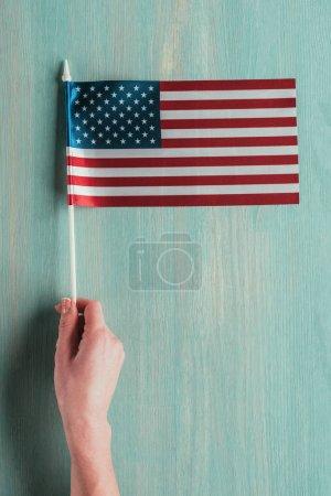 Photo pour Vue partielle de la femme tenant le drapeau américain à la main sur concept jour bleu en bois table, présidents - image libre de droit