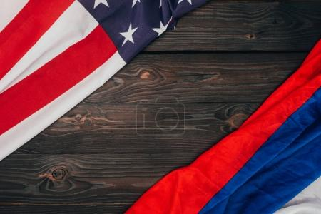top view of american and russian flags on dark wooden tabletop