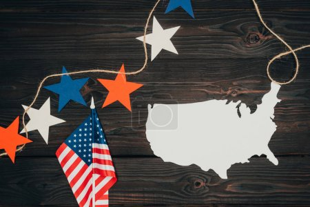 top view of arranged american flags, piece of map and stars on wooden surface, presidents day celebration concept