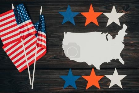 top view of arranged american flags, piece of map made of paper and stars on wooden surface, presidents day celebration concept