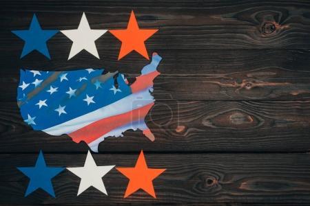 Photo pour Vue de dessus des étoiles disposées et morceau de carte avec drapeau américain sur la table en bois, concept de jour des présidents - image libre de droit