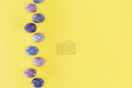 Photo pour Vue de dessus des œufs de Pâques peints en violet, isolés sur fond jaune - image libre de droit