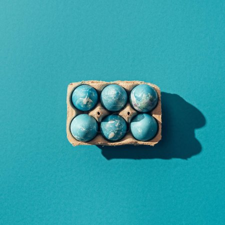 top view of blue easter eggs in tray, on blue