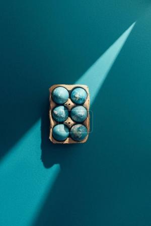 Photo for Top view of blue easter eggs in tray, on blue with sunbeam - Royalty Free Image