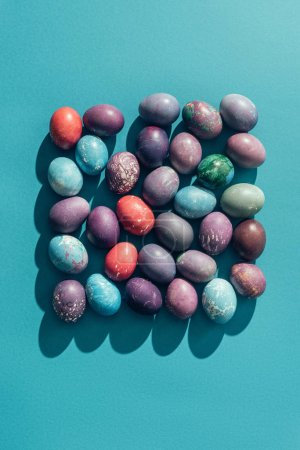 food composition with easter eggs in square shape, on blue