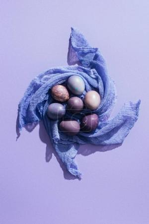 top view of traditional easter eggs on gauze, on purple