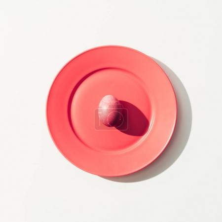 top view of shabby red easter egg on red plate, on white
