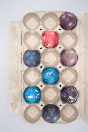 top view of painted easter eggs in tray, isolated on white