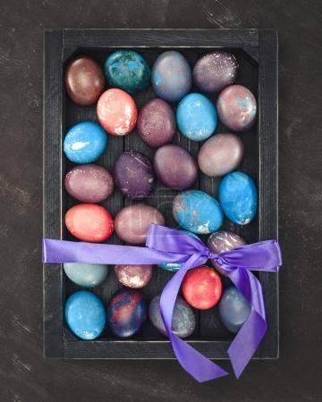 top view of painted easter eggs in gift box with bow
