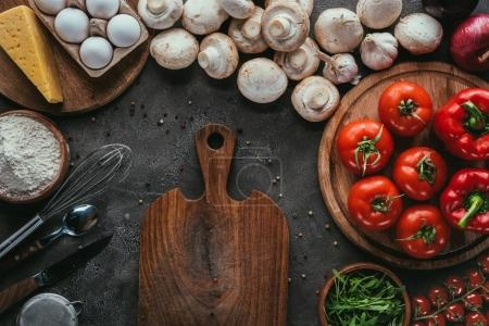 top view of different raw ingredients for pizza and cutting board on concrete surface
