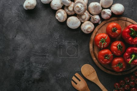 top view of raw tomatoes and mushrooms for pizza on concrete table