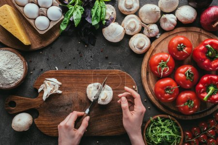 Photo for Cropped shot of woman cutting mushrooms for pizza on concrete table - Royalty Free Image