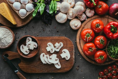 top view of various raw ingredients for pizza on concrete surface