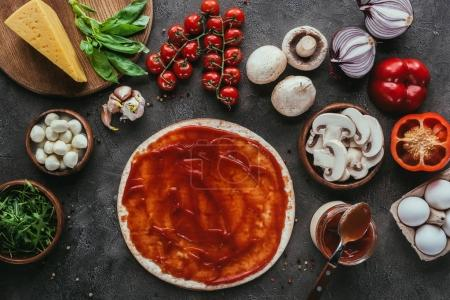Photo for Top view of uncooked pizza dough with sauce and vegetables on concrete table - Royalty Free Image