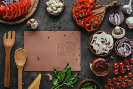 top view of pizza ingredients and blank paper on concrete table
