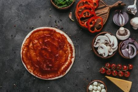 Photo for Top view of pizza dough with ketchup and vegetables on concrete table - Royalty Free Image