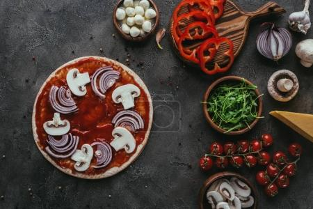 top view of unprepared pizza with ingredients on concrete surface