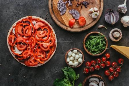 Draufsicht auf ungekochte Pizza mit verschiedenen Zutaten auf Betontisch