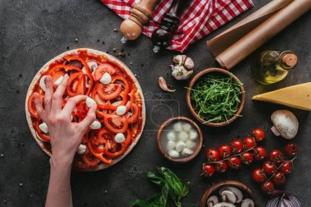 cropped shot of woman spreading mozzarella pieces onto pizza on concrete table