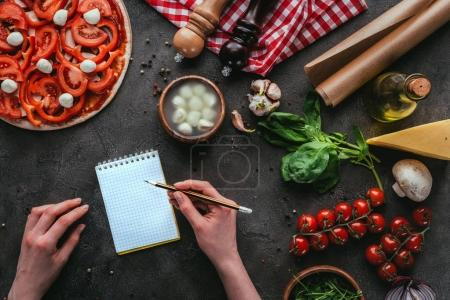 Photo for Cropped shot of woman writing notes while preparing pizza on concrete table - Royalty Free Image