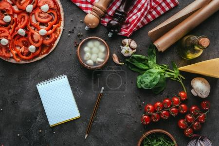 top view of uncooked pizza with notebook on concrete table