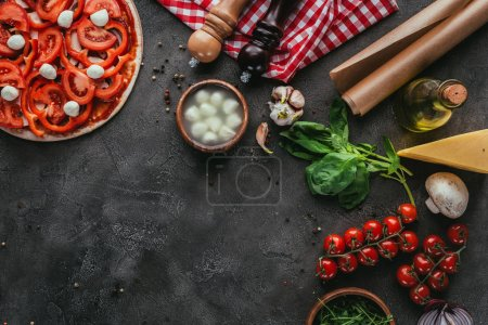 top view of raw pizza with ingredients on concrete table