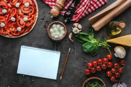 top view of uncooked pizza with blank notebook for recipe on concrete table