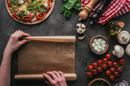 cropped shot of woman with parchent paper preparing pizza on concrete table
