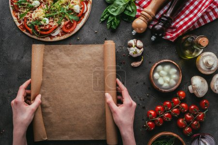 Photo for Cropped shot of woman with parchent paper preparing homemade pizza on concrete table - Royalty Free Image