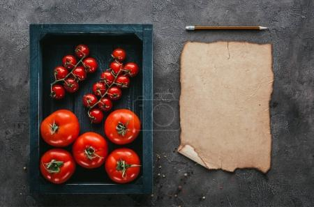 top view of tomatoes in box and blank paper on concrete surface