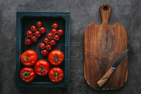 top view of tomatoes in box on concrete surface