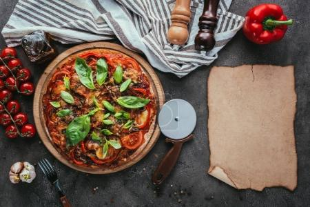 Photo for Top view of delicious pizza with cutter and blank paper on concrete table - Royalty Free Image