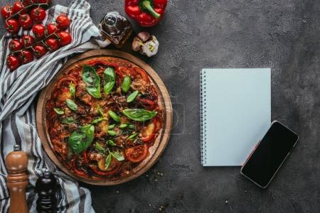 Photo for Top view of freshly baked pizza with notebook and smartphone on concrete table - Royalty Free Image