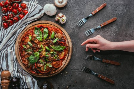 cropped shot of woman reaching for piece of pizza