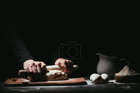 Photo for Cropped shot of person preparing dough with rolling pin on black - Royalty Free Image