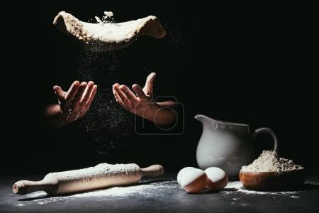 Photo pour Plan recadré du chef vomissant de la pâte pour la pizza sur noir - image libre de droit