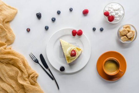 top view of piece of cake with berries and coffee on white table