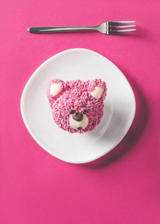 Photo for Top view of cupcake in shape of bear head on plate on pink surface - Royalty Free Image