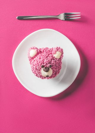 top view of cupcake in shape of bear head on plate on pink surface