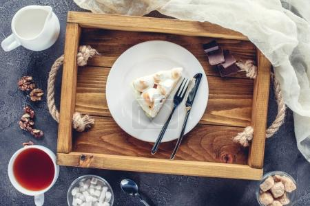 top view of delicious piece of cake with meringue on plate on wooden tray