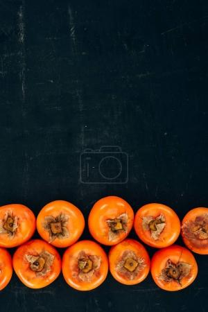 top view of rows of ripe yummy persimmons on black