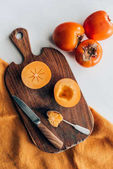 top view of persimmons on wooden board with knife and spoon