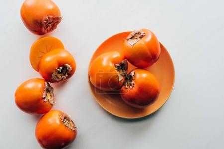 top view of persimmons on orange plate and on white tabletop