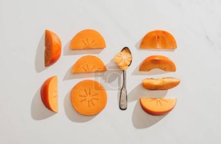 elevated view of persimmons pieces and spoon on white