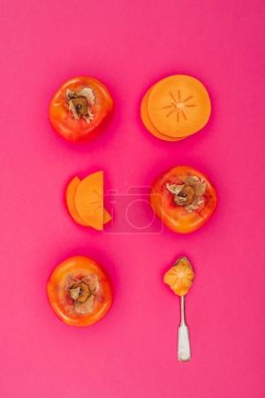 top view of persimmons pieces and spoon isolated on pink
